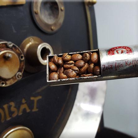 Röstprobe in der Kaffeerösterei Cafe Fino gehalten von Thomas Michel - der Kaffeeröster ist im Hintergrund erkennbar und das Cafe Fino Logo befindet sich auf dem Metall der Röstprobe - die braunen Kaffee Bohnen liegen in einer Aussparung mit Metall an einem Holzgriff