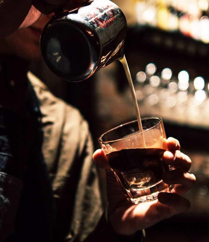 Mann schüttet Milch in Glas mit Espresso und auf dem metallenen Milchkännchen befindet sich das Cafe Fino Kaffeerösterei Logo - im Hintergrund ist das Regal der Bar verschwommen erkennbar mit Flaschen und Gläsern, in denen sich das Licht spiegelt