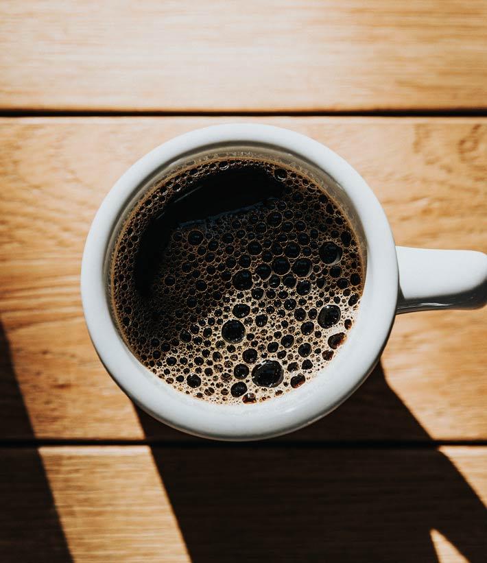 Schwarzer Kaffee oder Espresso in weißer Kaffeetasse von Oben sichtbar mit Schattenwurf, auf Holzuntergrund