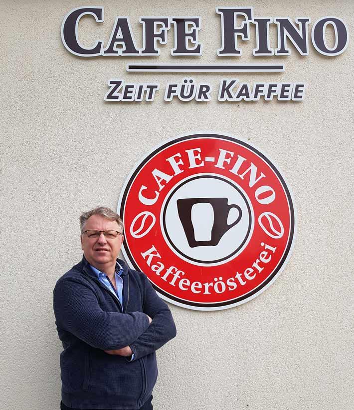 Thomas Michel vor dem rot weißen Cafe Fino Kaffeerösterei Logo an der Außenwand in Mammendorf, mit Zeit für Kaffee in brauner Schrift darunter- Thomas verschränkt die Arme und sieht fröhlich aus während er stolz auf seine 30 jährige Rösterei in die Kamera blickt