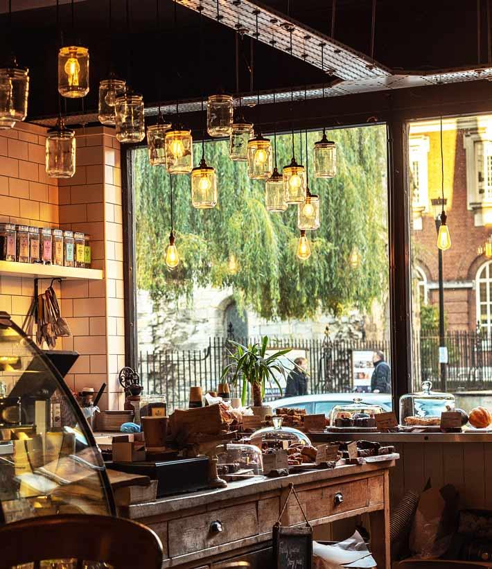 Das Innere einer Bäckerei und Konditorei mit Ausblick vor dem Geschäft wo sich zwei Personen unterhalten - im Geschäft leuchten gelbe Lampen mit Flaschenlampenschirm an der Decke - es befinden sich Backwaren Kaffee Tee und Espresso im Verkauf hinter der Theke